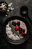 A smoothie bowl with berries, coconut and chia seeds
