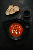 Tomato soup garnished with cream and olive oil with toasted bread