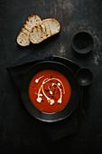 Tomatensuppe garniert mit Sahne und Olivenöl dazu Röstbrot