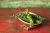 Green peppercorns in a wooden bowl