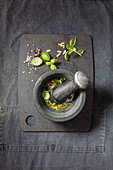 Mortar and pestle with herbs, olive oil and garlic