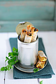 Potato and olive briks with lemon and parsley in a tin can
