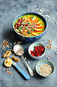 A green smoothie bowl with spinach, kiwi, nectarines, figs and pomegranate seeds