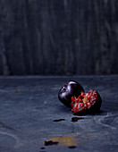 Red plums, whole and halved, against a dark background