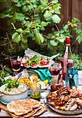 Grillbuffet mit Fleisch, Wurst, Fladenbrot, Salat und Wein