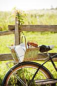 Fahrrad mit Picknickkorb an einem Holzzaun auf der Wiese