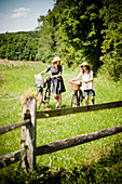 Two girls pushing bicycles with picnic baskets