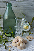 Vanilla crescent biscuits, shot glasses and damson water in a green bottle