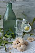 Vanillekipferl, Schnapsgläser und Zwetschgenwasser in grüner Flasche