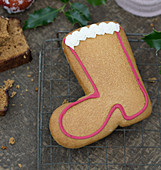 A gingerbread boot biscuit decorated with meringue