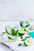 Two glasses with classic mojito, lime wedges and mint leaves on a white wood cutting board