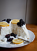 Angel food cake with whipped cream, lemon slices and blackberries