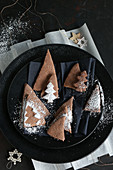 Gluten-free chocolate triangle and Christmas tree-shaped biscuits with icing for Christmas