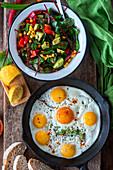 Spiegeleier und Salat mit Mais, Avocado und Paprika