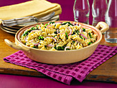 Rotini with broccoli and red onions in a baking dish