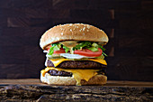 Double Burger with american cheese, lettuce and tomato on on a dark rustic background