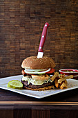 Burger with blue cheese, lettuce, deep fried onions, fries, pickle and tomato on a dark rustic background with a knife