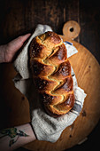 Hands holding challah bread (Jewish cuisine)