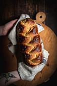 Hände halten Challah-Brot (jüdische Küche)