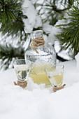 Birnenschnaps in zwei Gläsern und Karaffe im Schnee