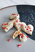 White chocolate coated heart shaped biscuits decorated with freeze dried strawberries and glitter