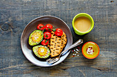 A healthy breakfast: avocado with eggs served with crackers, tomatoes and coffee