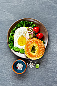 A vegetarian breakfast with a bagel, a fried egg and vegetables (seen from above)