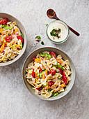 Farfallesalat mit Tomaten, Paprika, Petersilie, Zwiebel und Joghurtdressing
