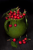 Ripe cherries in ceramic pitcher on black background