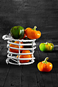 Yellow and green Hungarian tomato peppers in white basket, on black wooden background