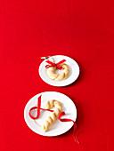 Weihnachtsplätzchen mit Dekoband auf weißem Teller, auf rotem Untergrund