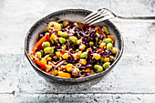Colourful quinoa salad with tomatoes, sweetcorn, edamame, red cabbage, roasted chickpeas and carrots