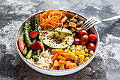A Buddha bowl with bulgur, green asparagus, strawberries, carrots, tofu, tomatoes, sweetcorn, sweet potatoes and avocado