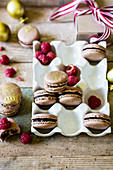 Festive chocolate macarons with gold dust in white holder with raspberries