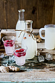 Festive gingerbeer in bottles and glasses served with raspberries on a rustic wooden surface with ice as a gift