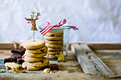 Stack of festive turkish delight biscuits with reindeer decoration as a gift with white background and wood
