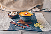 Spicy asian pumpkin soup garnished with red chillies, limes, and pumpkin seeds, topped with coconut cream