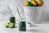 Spirulina and green fruit smoothie in glass jars, halved kiwi and limes, a big white bowl of assorted fruit on a light colored tabletop