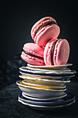 Three raspberry macaroons on a stack of plates