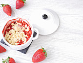 Strawberry crumble in a baking dish on a wooden board