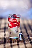 A quark dessert with red fruit in a glass