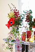 Weihnachtsdekoration mit Anemonen, Kerzen und Lichterkette auf Kaminsims