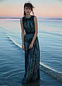 Dunkelhaarige Frau in langem, Abendkleid bei Sonnenuntergang am Meer