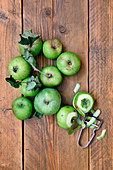 Green organic apples with leaves on a wooden background