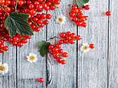 Redcurrants with leaves and flowers on a wooden background