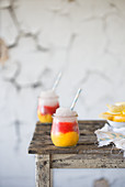 Layered cocktails with mango, strawberry and vodka in glasses on a wooden table