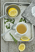 Hot lemon tea with dried lemon leaves on a metal tray
