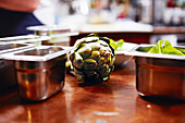 Artischocke zwischen Metallbehältern in Küche