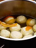 Topfenknödel mit Orangenschale im Wasser ziehen lassen