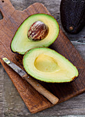 A halved avocado with a stone and a knife on a rustic wooden board